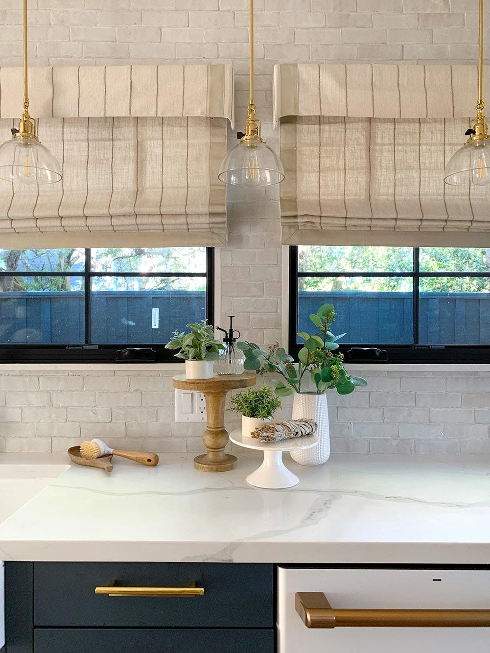 windows over kitchn counter with light beige striped roman shades and brass pendant lights
