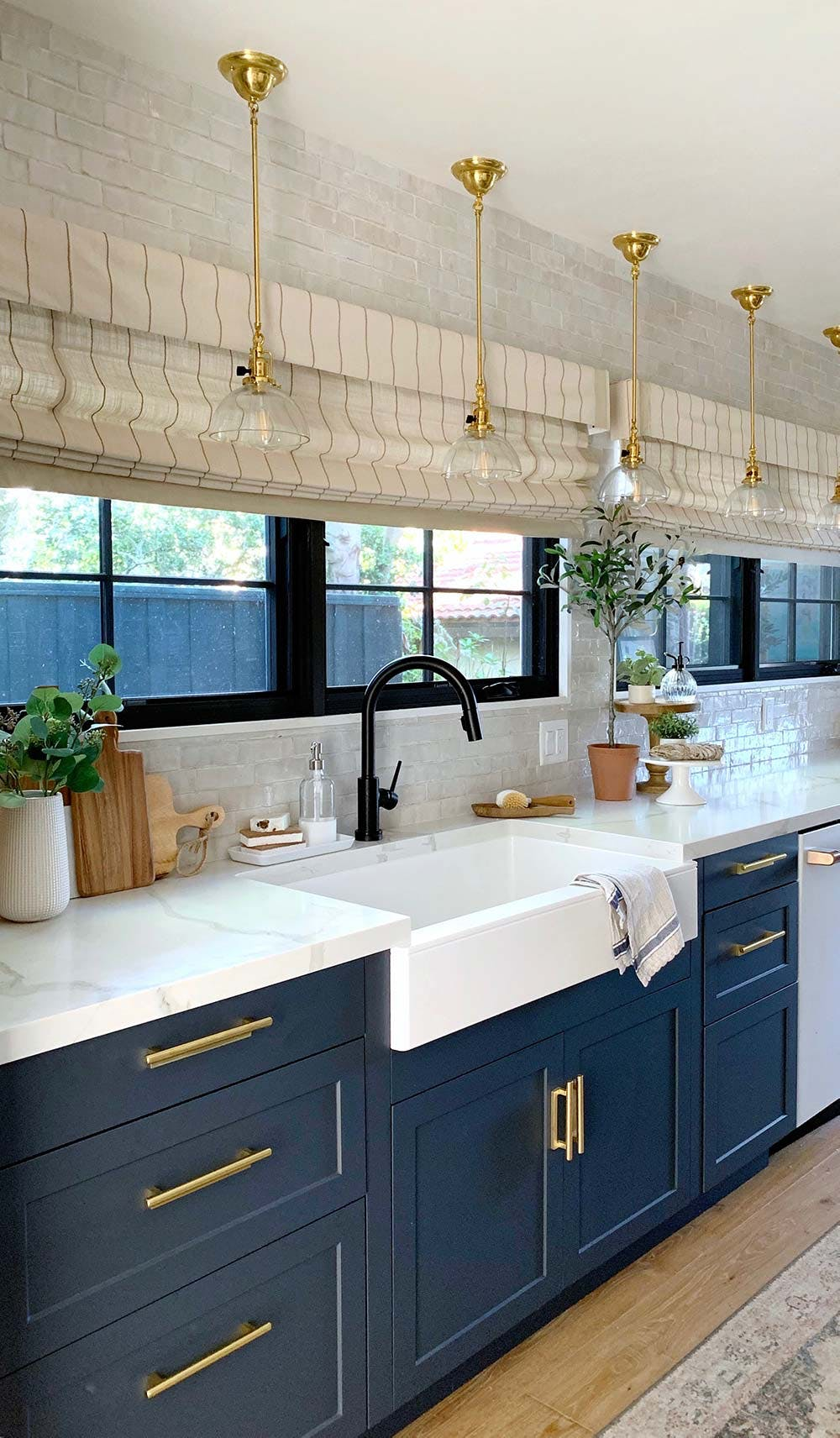 galley kitchen with navy blue cabinets, white marble counters and linen striped roman shades