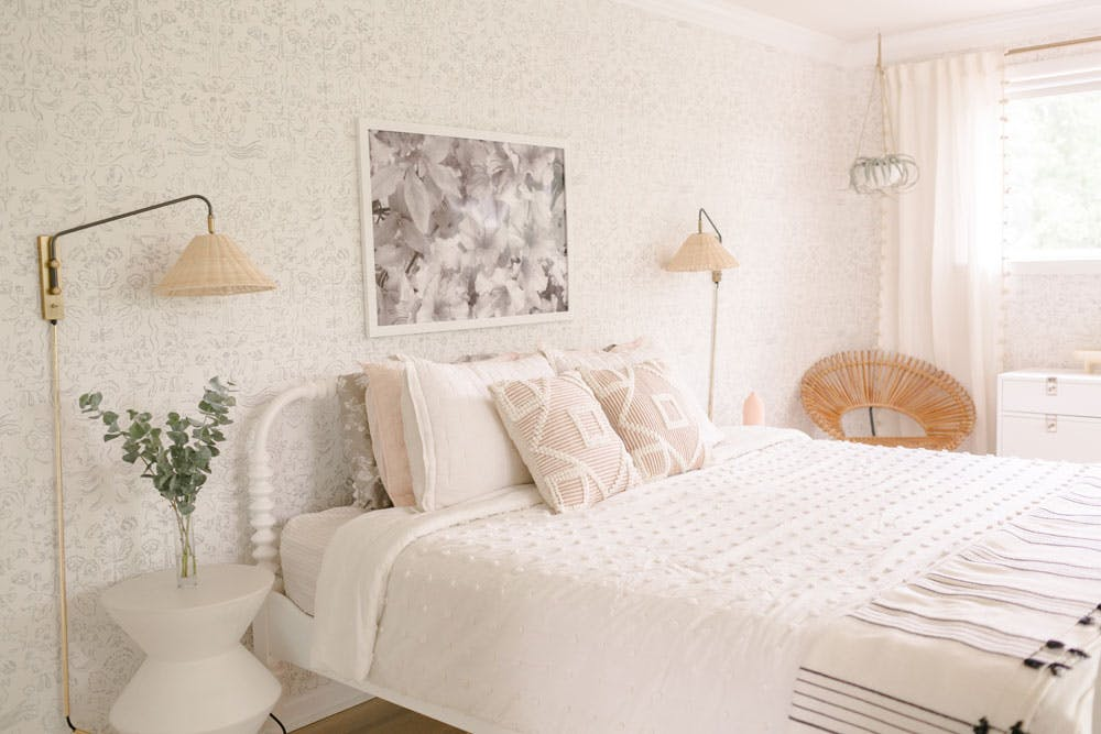 neutral bedroom with wallpaper and wicker lamps mounted to wall