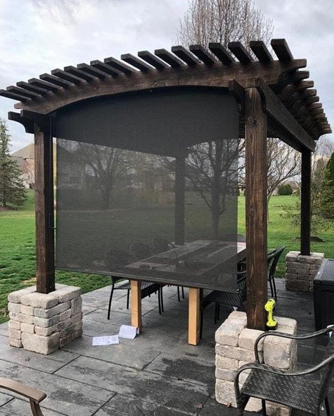 Wood pergola over a patio table and chairs that is shielded by a black, lowered outdoor solar shade.