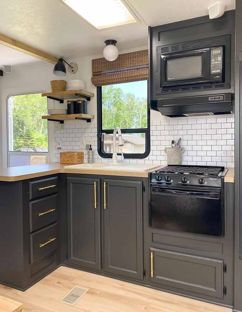 Updated RV kitchen with painted grey cabinets, wood shelving and woven wood shades over the window.