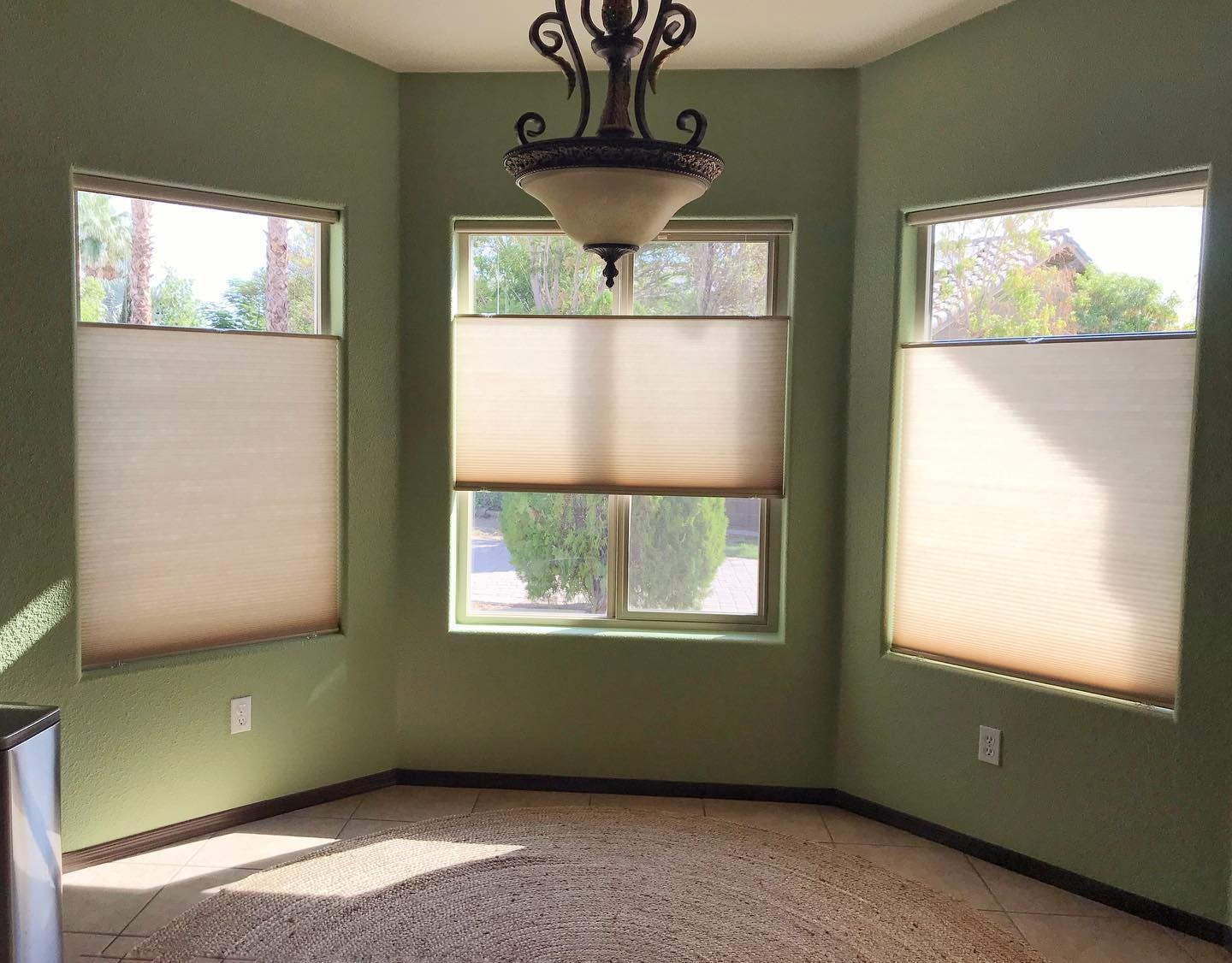 bay window in an empty room that is covered with pale gold cellular shades.