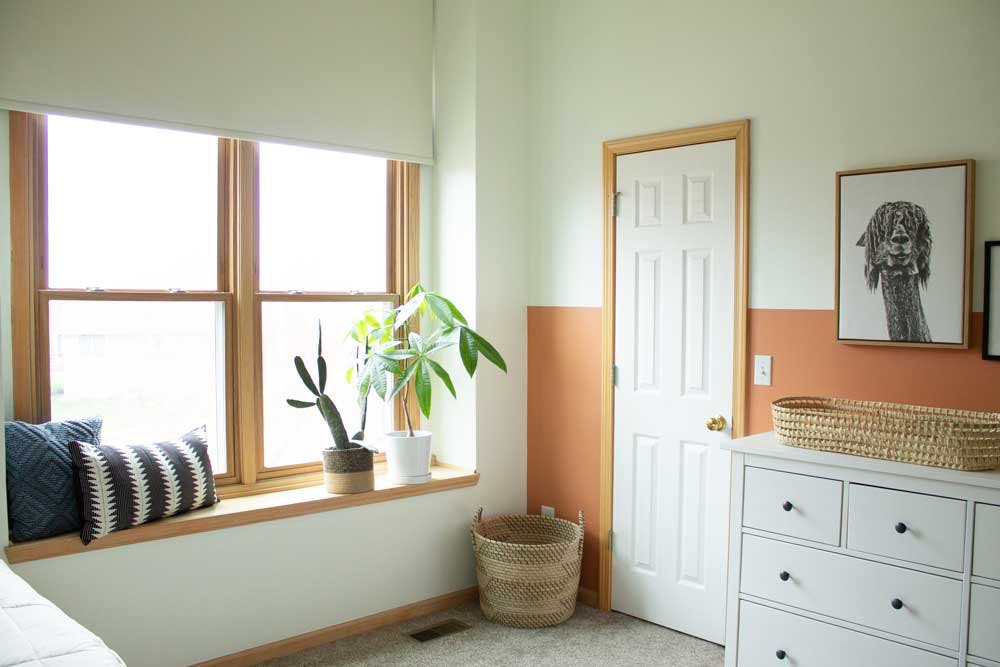 white roller shades over window seat