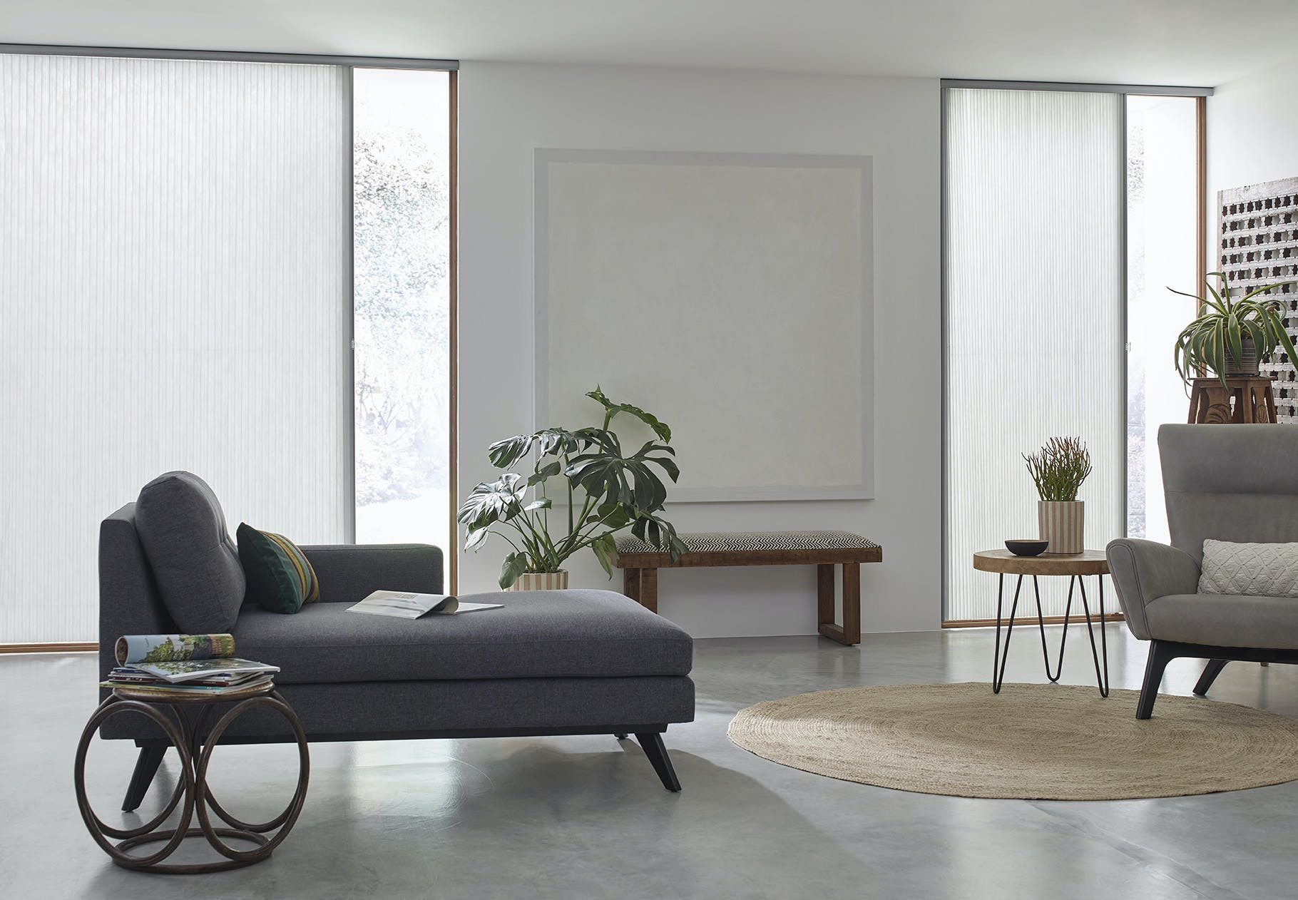 Modern, grey toned living room with two large sliding glass doors covered with white, light filtering vertical cellular shades.