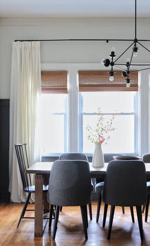 dining room with grey upholstered chairs and bamboo blinds
