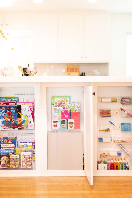 kids art storage in cabinets under kitchen island