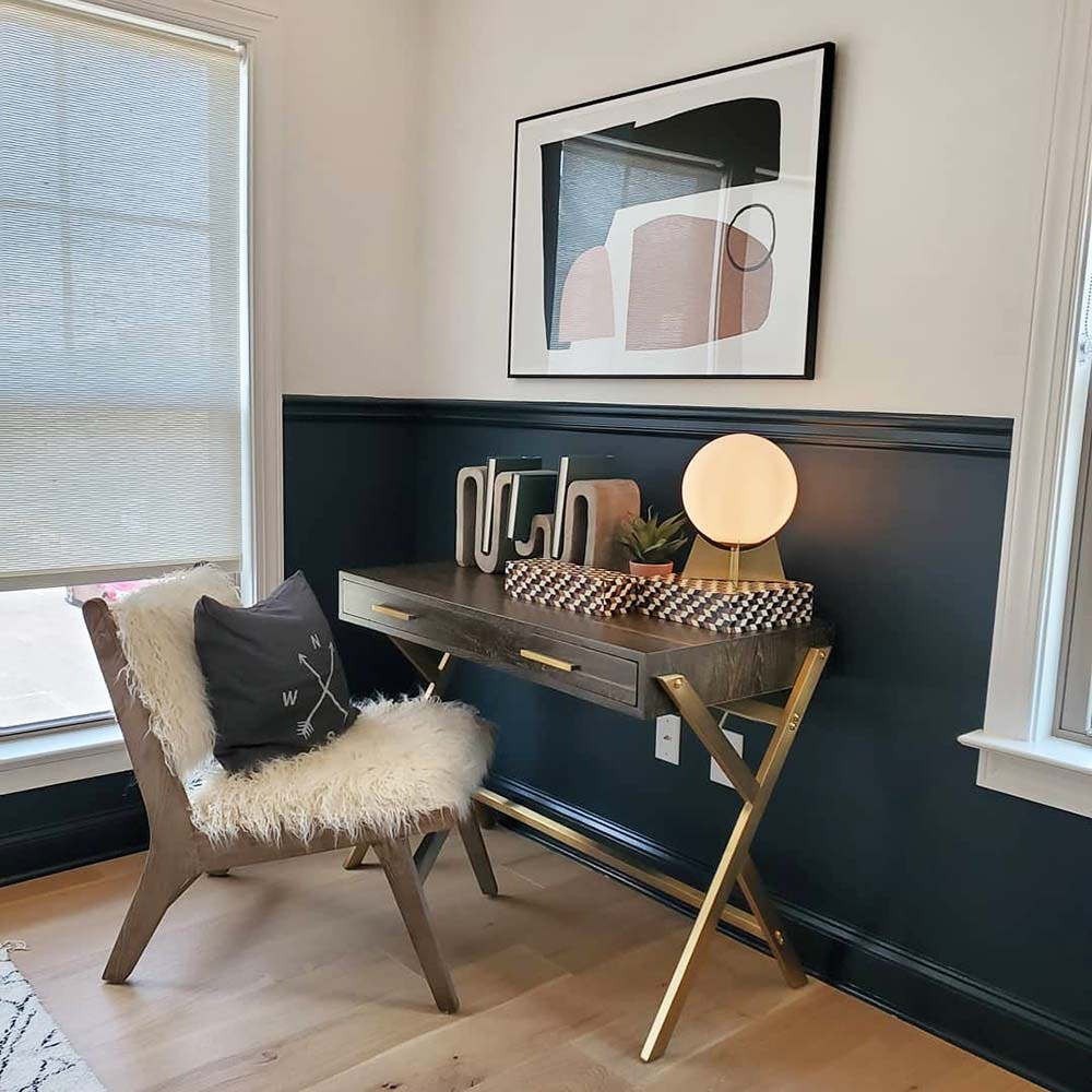 Brass and wood writing desk pushed into a corner near a window with a fluffy, white faux fur chair.