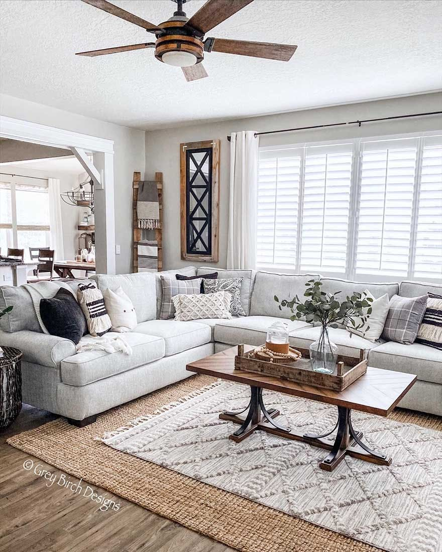 Modern farmhouse living room with grey couch and white plantation shutters.