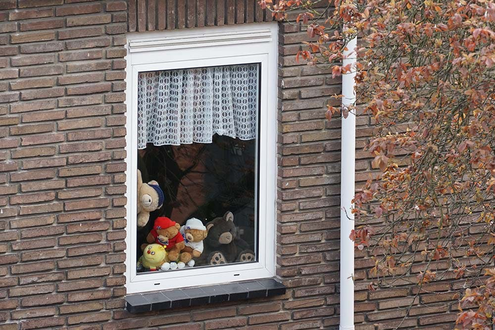Window with stuffed animals stacked on the sill, facing outside.