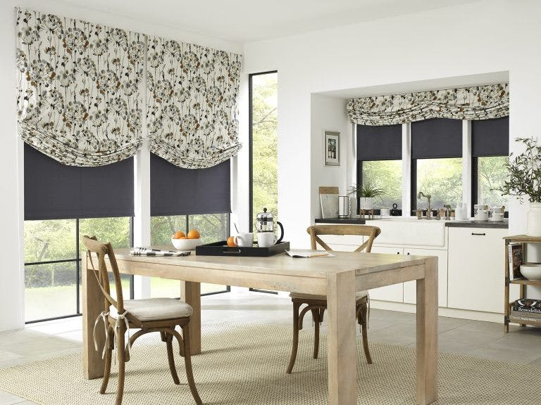 farmhouse kitchen with roman shades installed over blackout roller shades