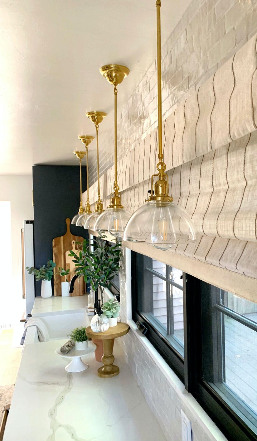 look down long bank of windows in kitchen with pinstripe shades and brass pendant lights