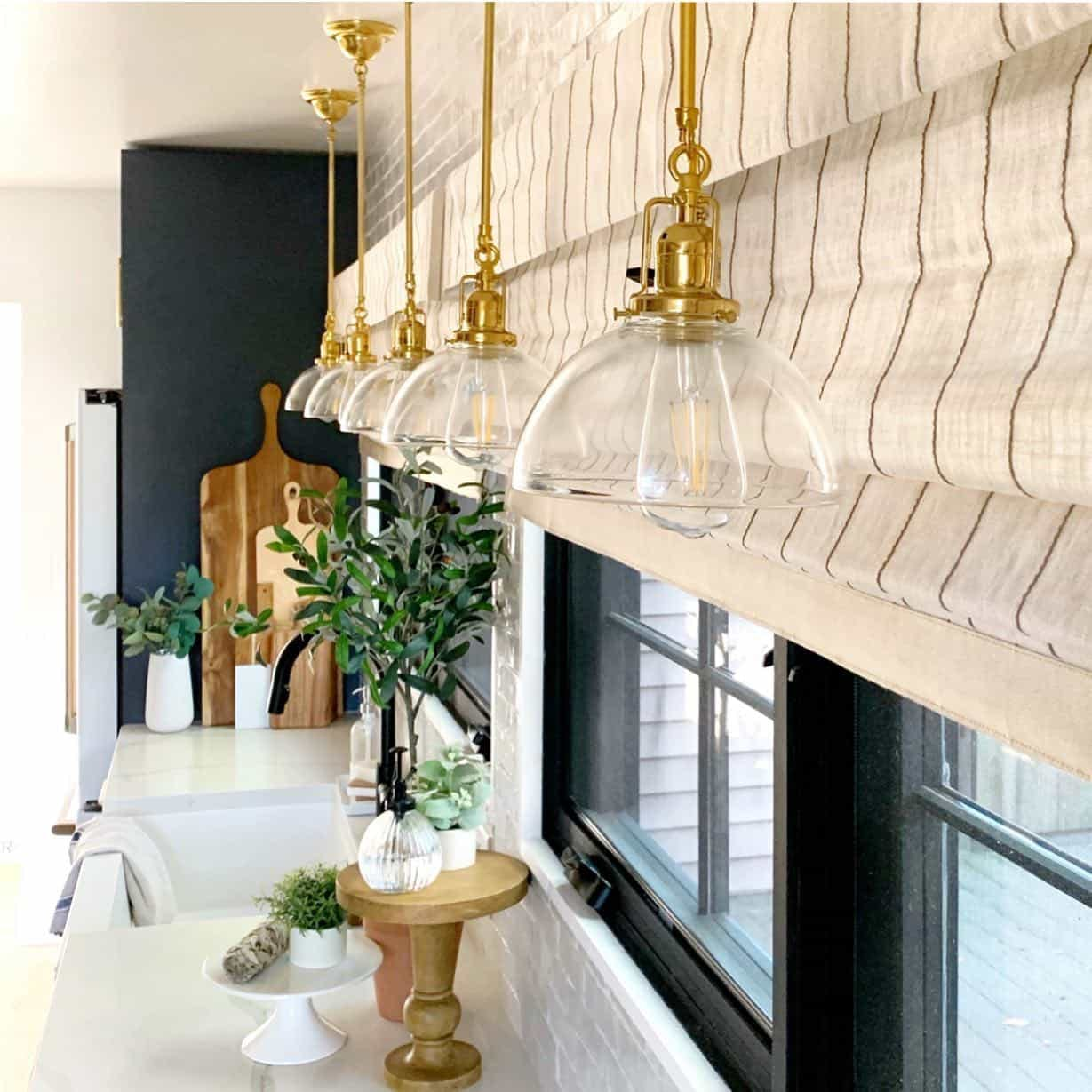 Kitchen windows with cream roman shades and brass pendant lights.