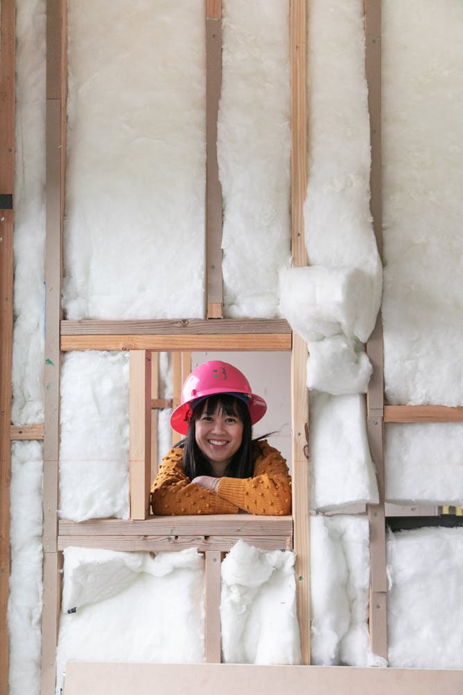 woman looking through framed window with insulation on construction project