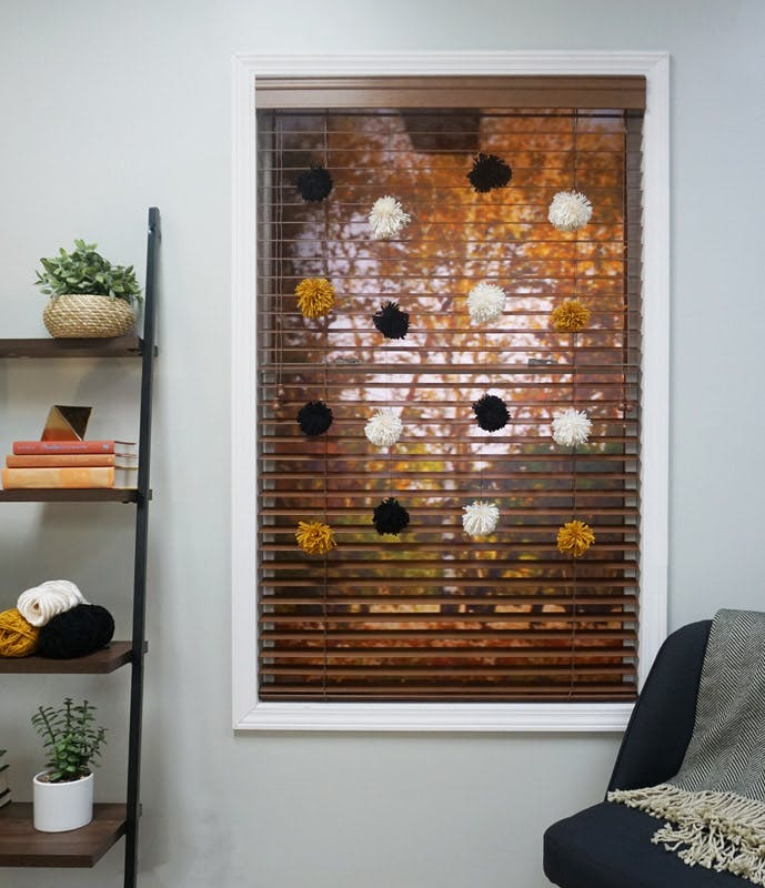 Brown wood blind with fall colored pom pom strands hung in the window.
