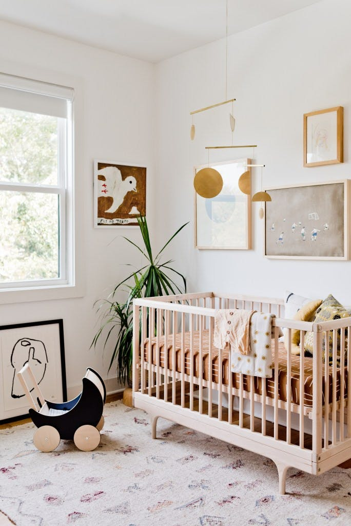 modern nursery with blonde wood crib, brass mobile and white roller shade