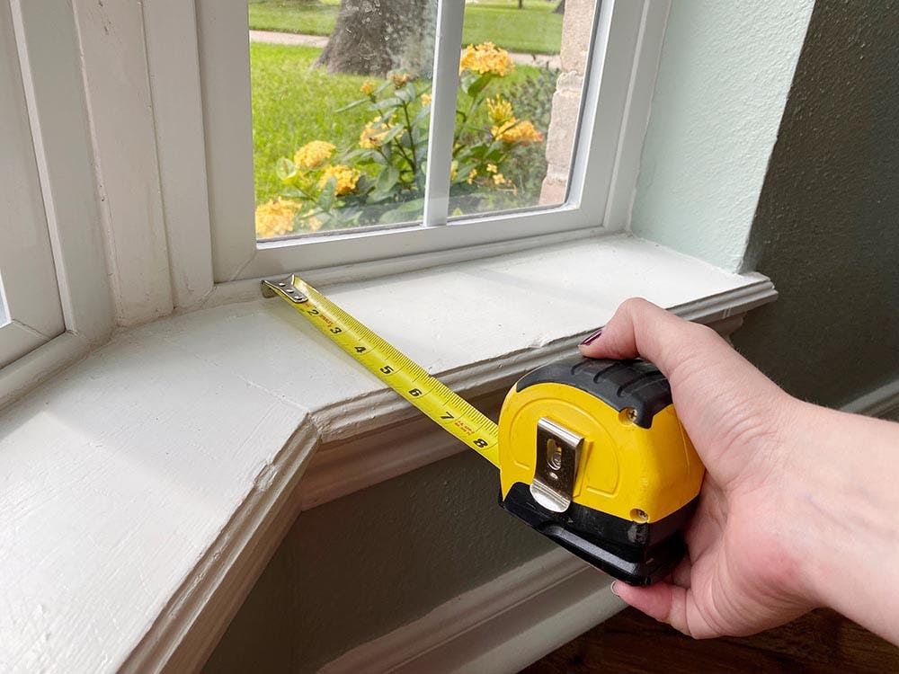 a hand using a steel tape measure to check the. depth of a bay window.