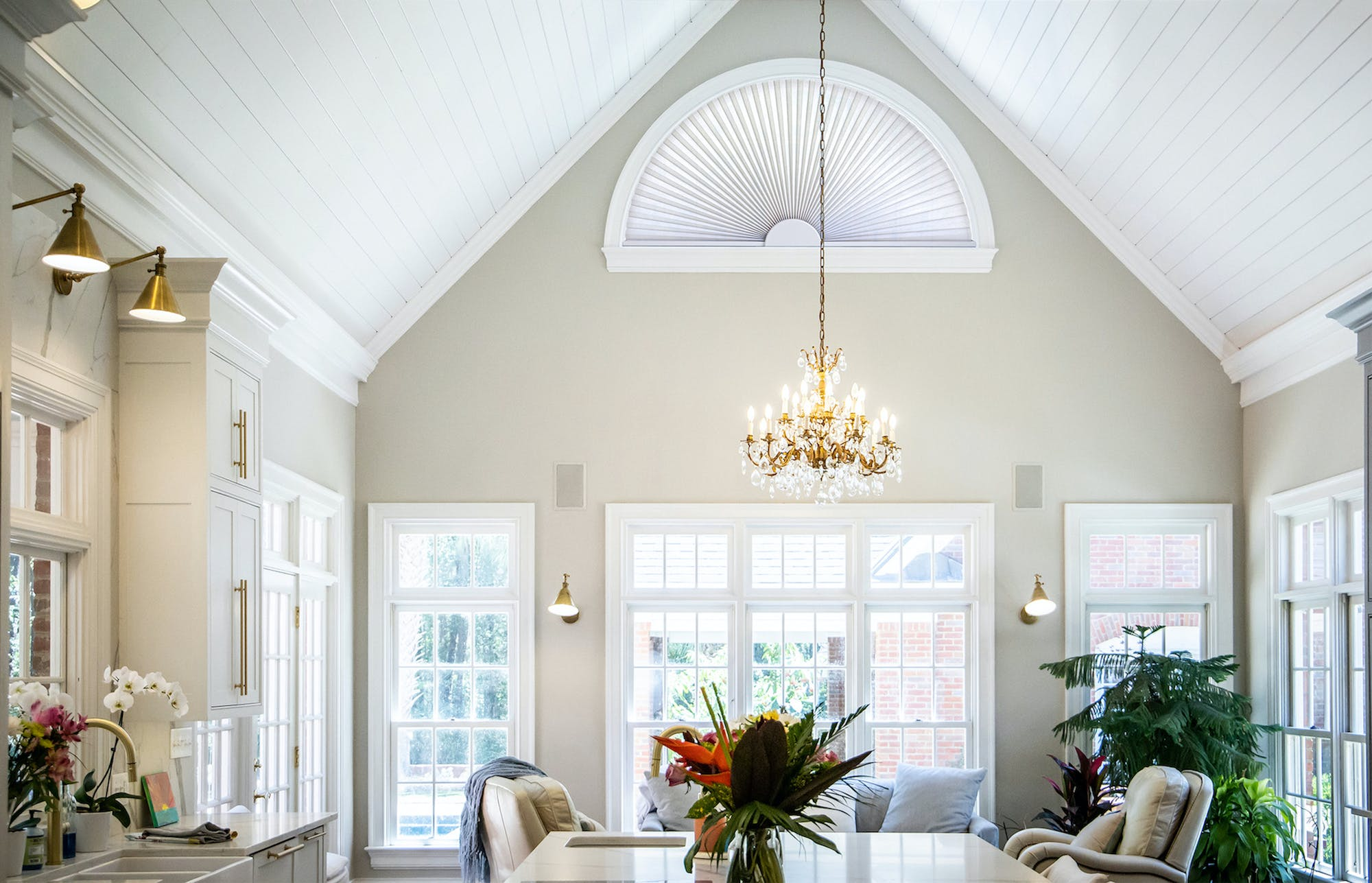 Contemporary living room with a gabled ceiling with a large arched window covered with a light filtering solar shade.