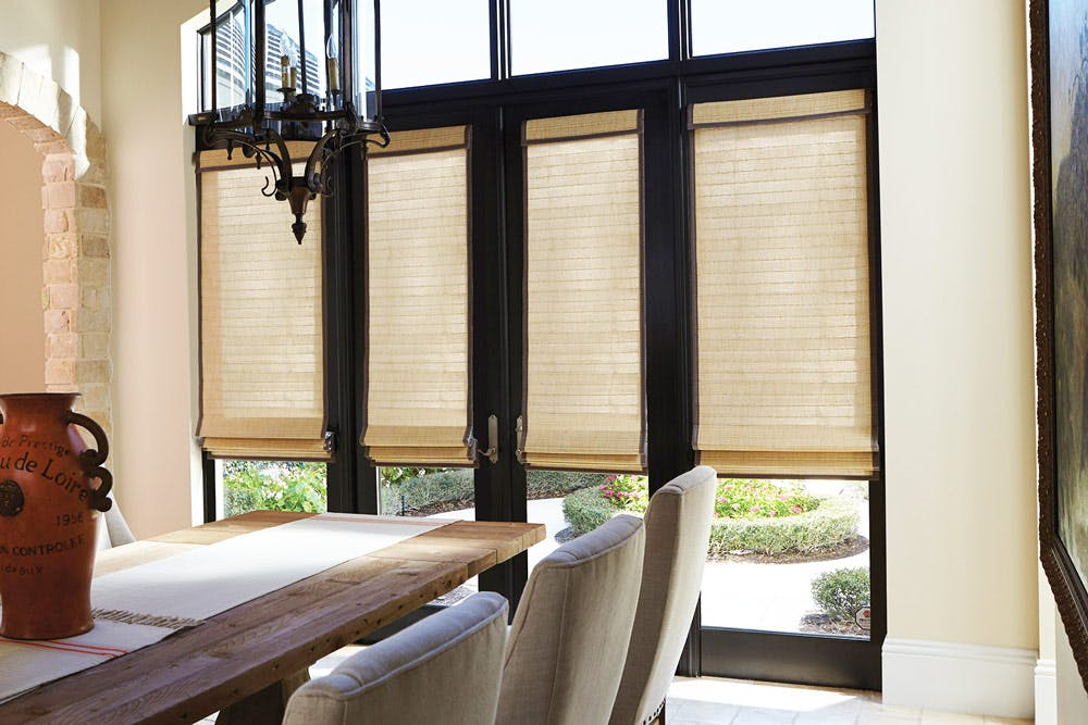 Roman shades installed over floor tall french doors in a traditional dining room.