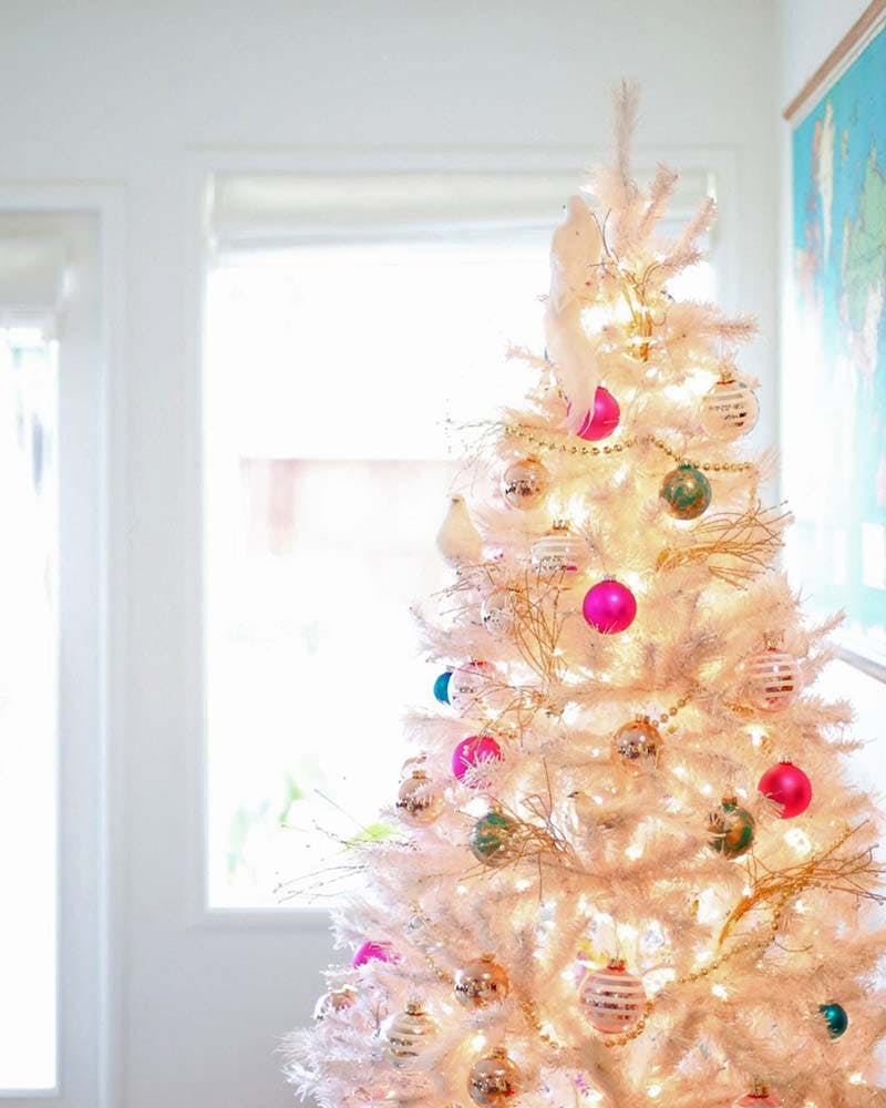 White christmas tree with hot pink and blue ornaments next to an open window.