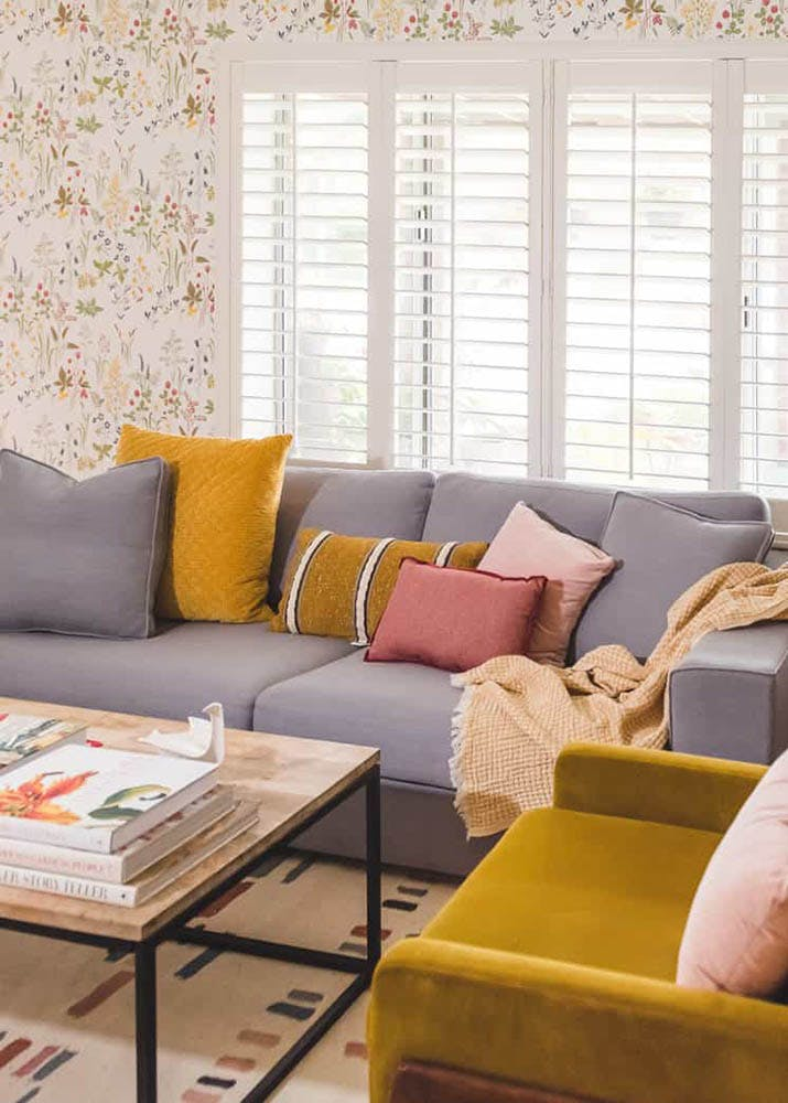 Vintage inspired living room with modular furniture, floral wallpaper and white plantation shutters.