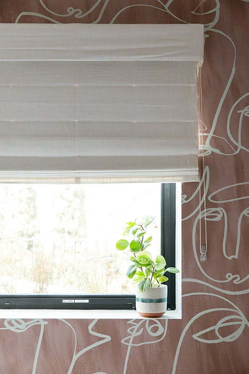bedroom with pink abstract face wallpaper and white blackout roman shades on window