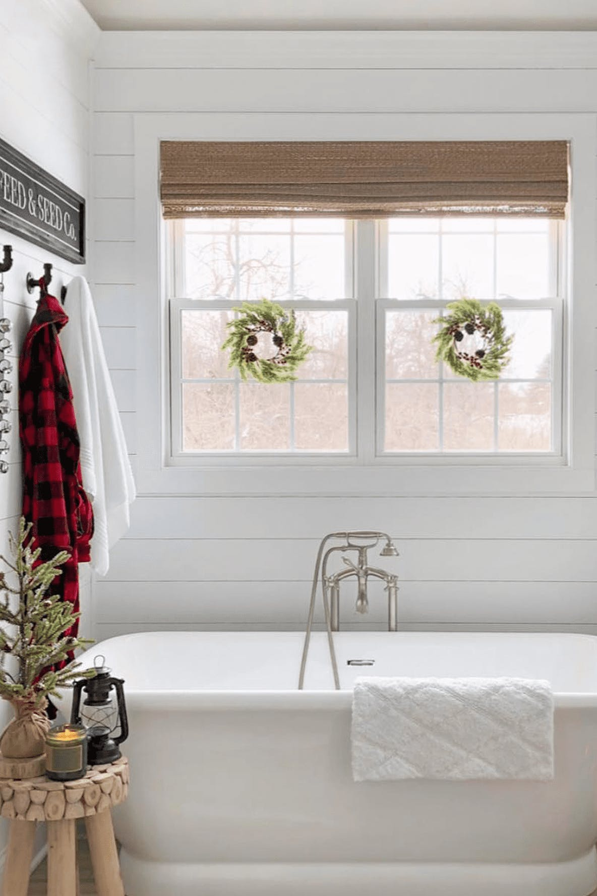 Bathroom window with woven wood shade and two holiday wreaths over the glass.