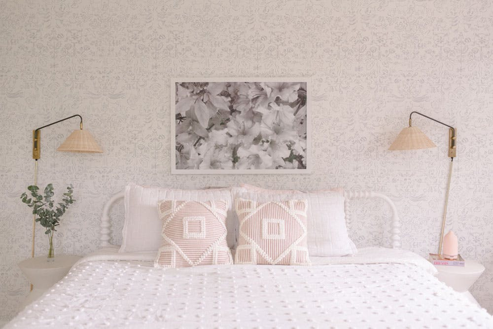 bed with white bedding, blush pillows and wicker sconces over nightstands