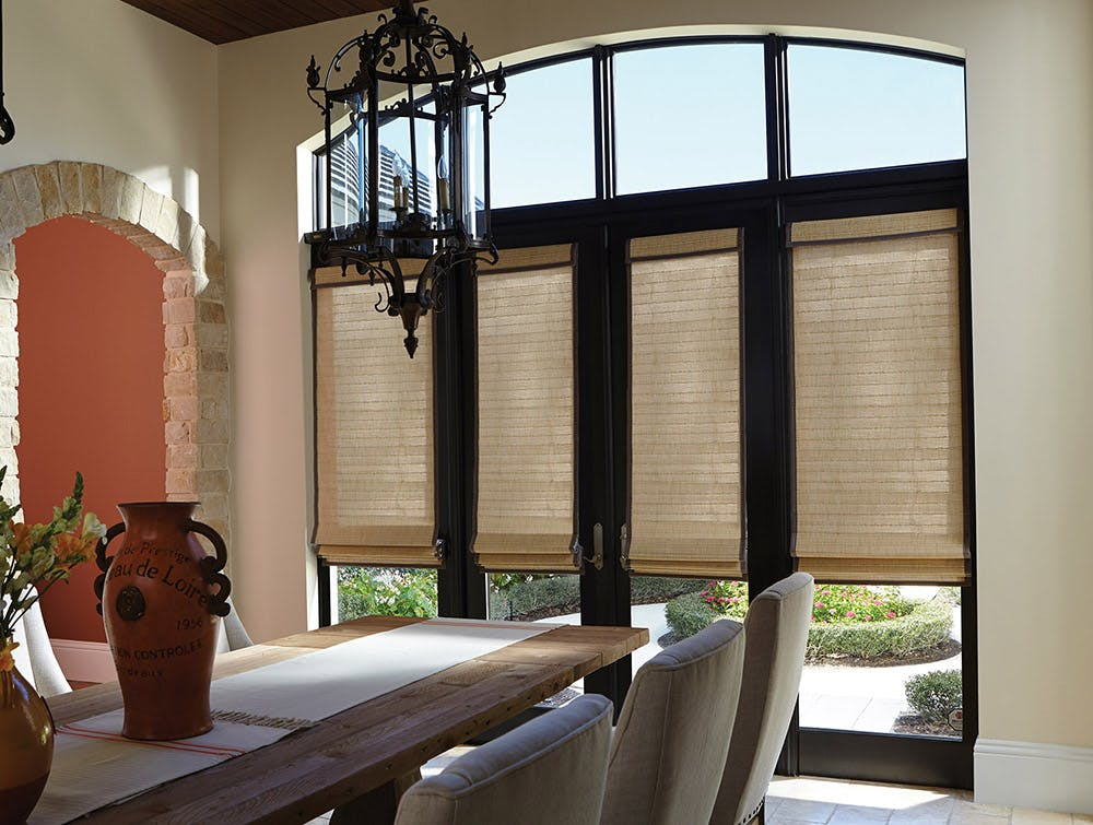Traditional, mediterranean inspired dining room with tall french doors and beige roman shades.