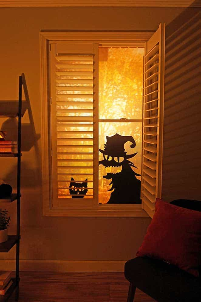 Backlit window shutter with one panel open revealing a witchy silhouette decoration.