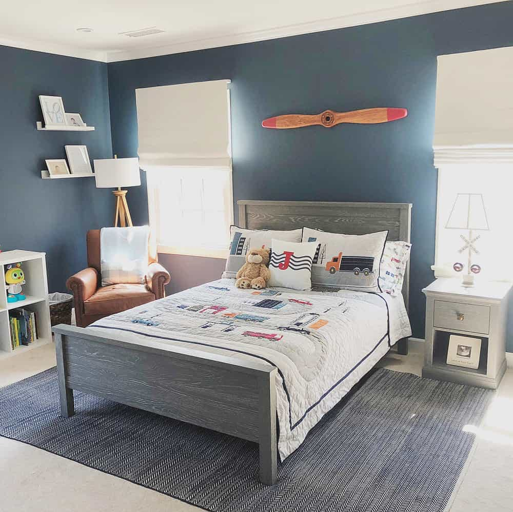 Planes, Trains and automobiles themed boy's room, dark blue walls and off white roman shades on either side of a grey bedframe.