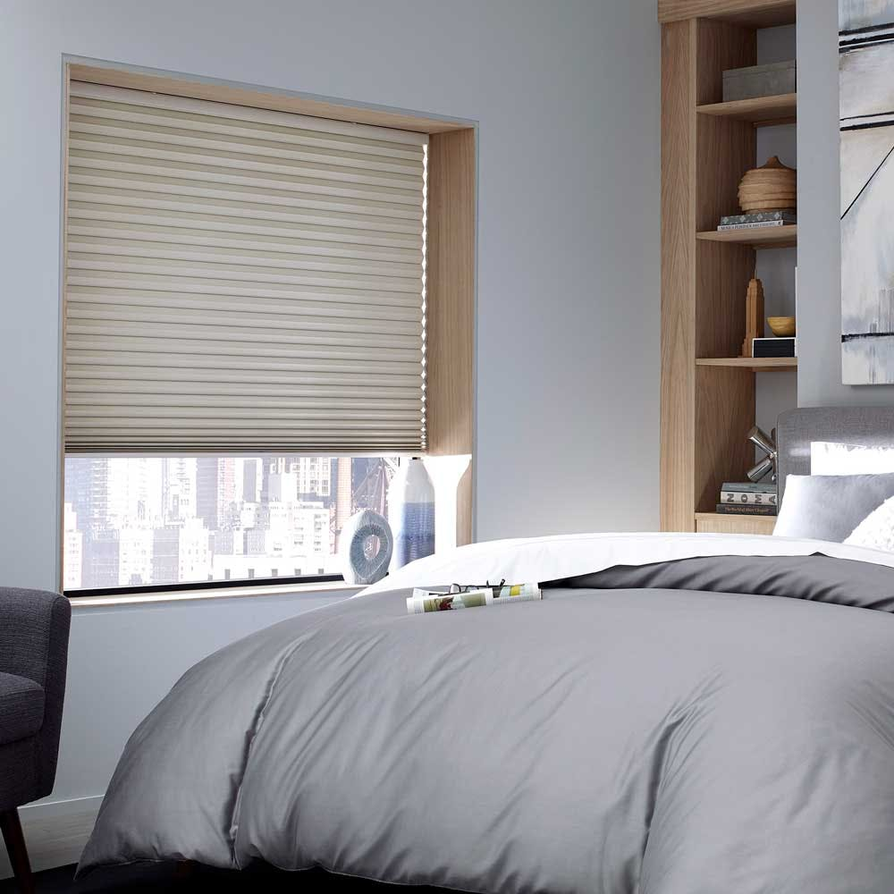 modern bedroom with a beige blackout cellular shade partially lowered in the window.