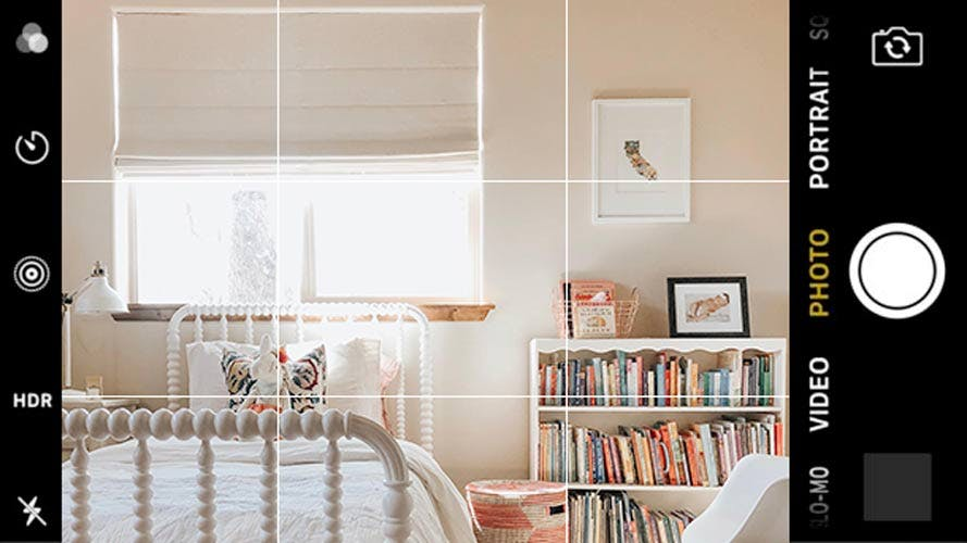 neutral toned kids bedroom with full bookshelf and blackout roman shade in window.