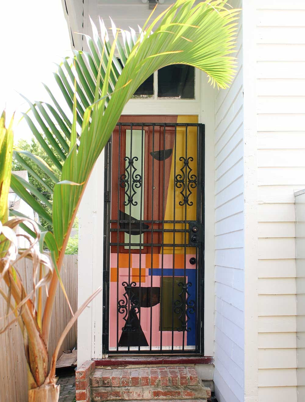 colorful geometric mural painted on back door with wrought iron grate