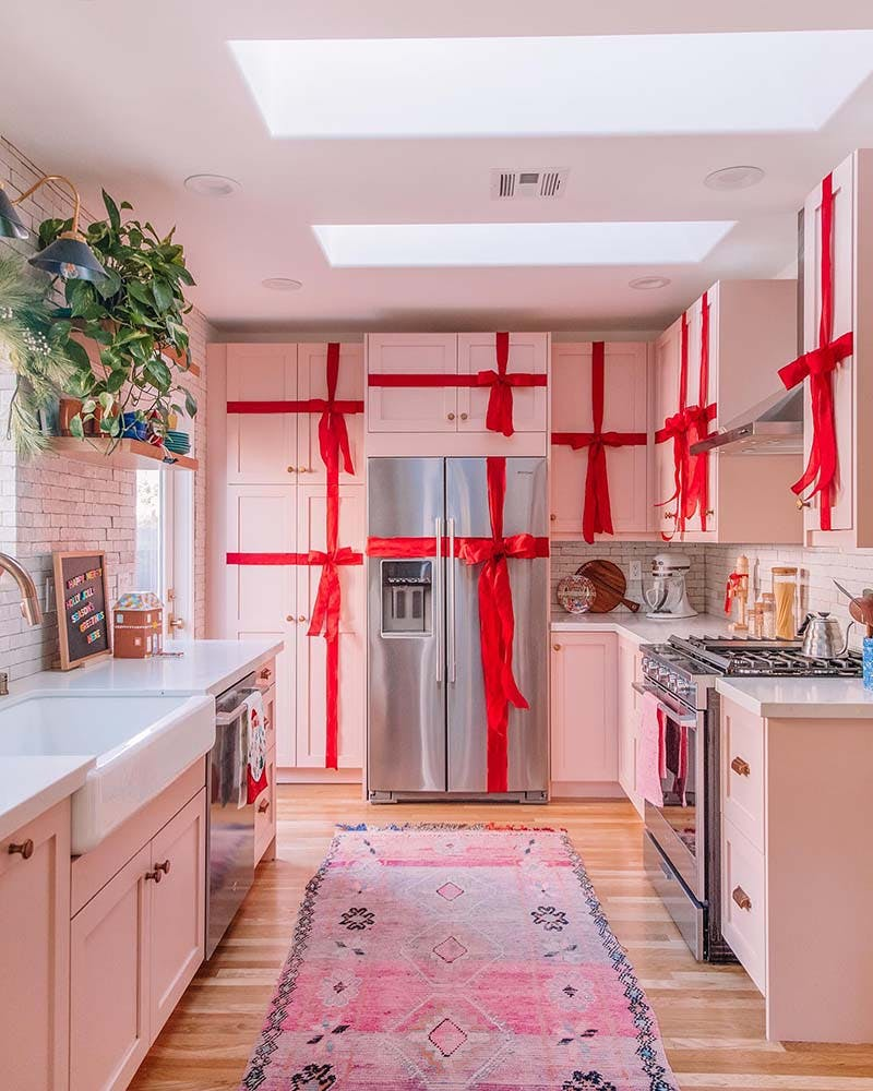modern vintage kitchen with pink cabinets wrapped with red ribbon.