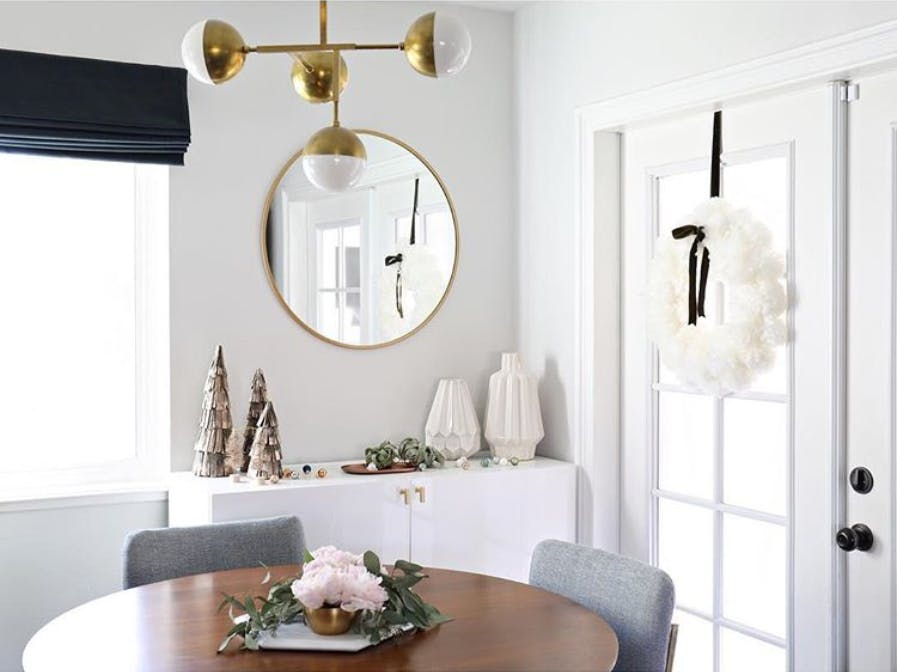 Dining room with roman shades on the windows and french doors decorate with white wreaths.