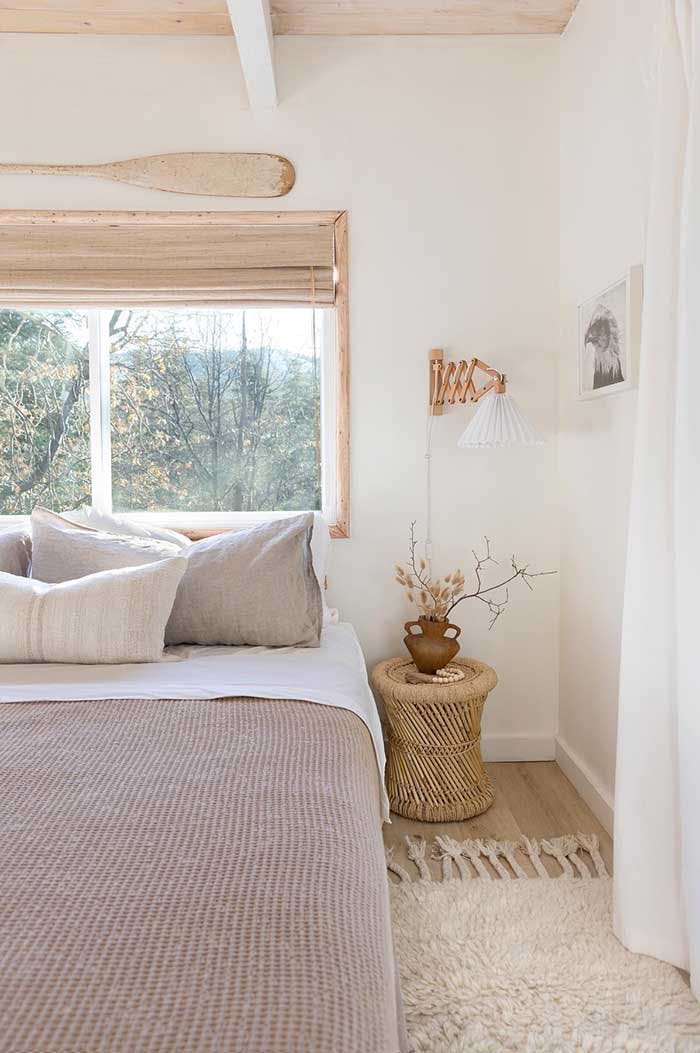 Bright, neutral toned bedroom with a window and woven wood shade over the bed.