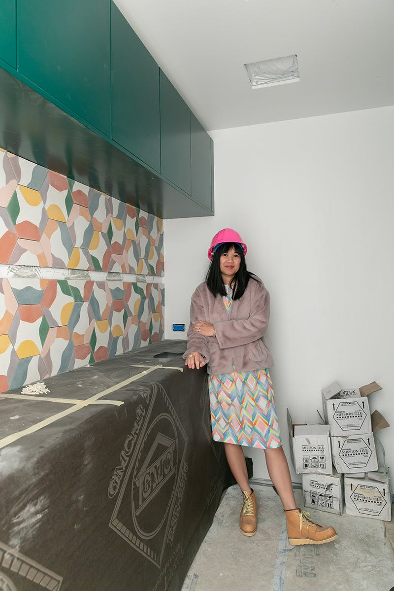 woman standing in laundry room under construction with colorful tile backsplash