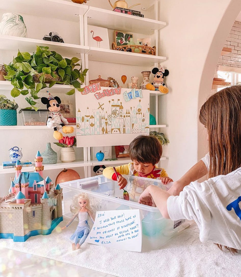 toddler and mom playing in plastic tub at kitchen table