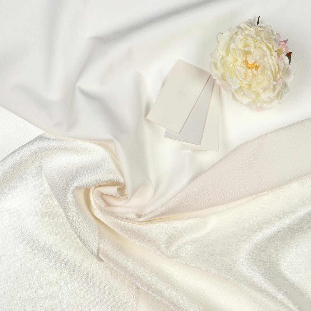 White drapery fabrics coiled around each other, three faux wood blind samples and a white peony flower.