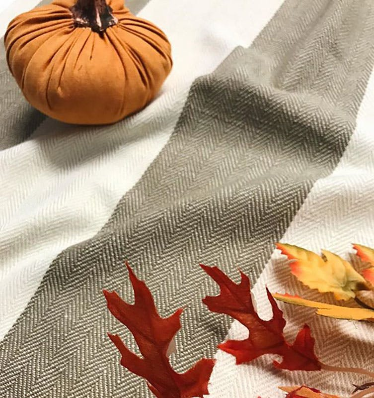 white and grey striped fabric with subtle herringbone texture draped across a flat surface and accented with a small stuffed pumpkin and sprig of orange leaves.