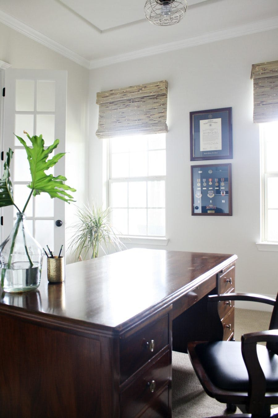 home office with large, wood desk and woven wood shades over the two windows.