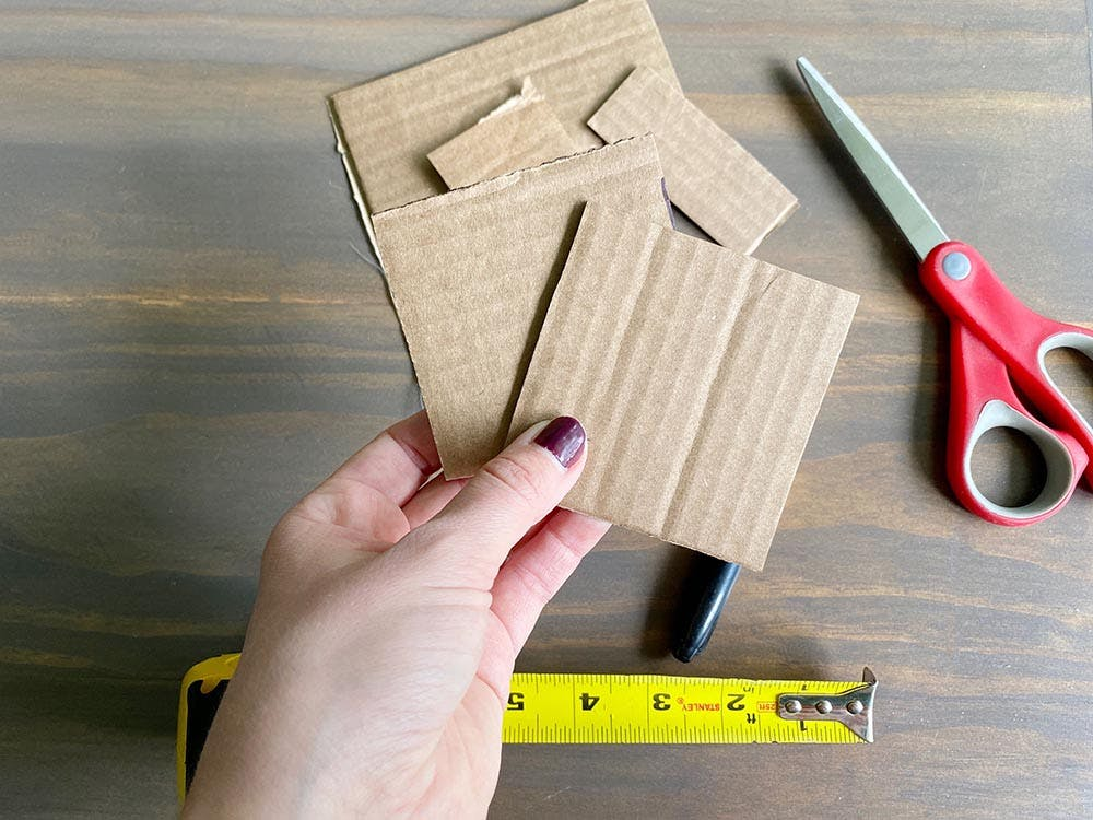 a hand holding two small cardboard squares to use as a bay window measuring template.