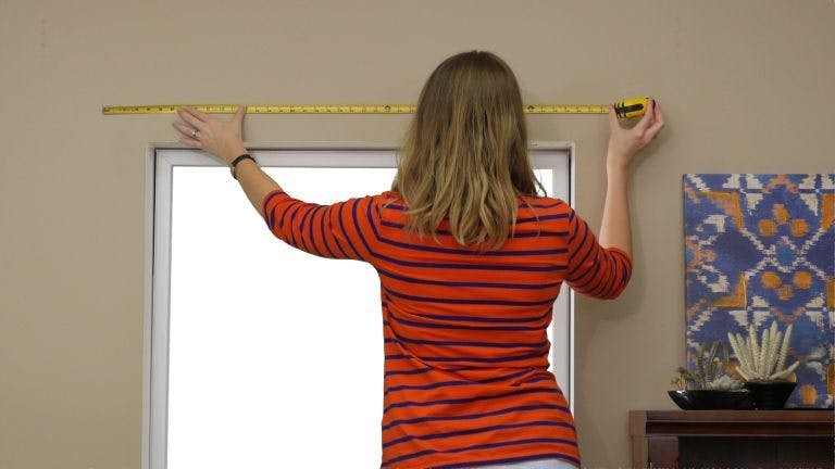woman in red striped shirt measuring space above window to install blinds
