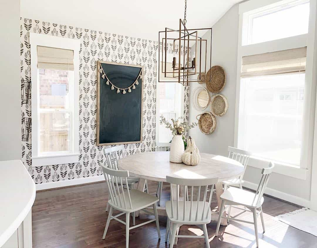 Modern farmhouse dining room with floral wallpaper and a large chalkboard between the woven wood window shades.