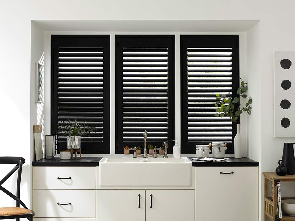 modern kitchen sink with white cabinets and black shutters.