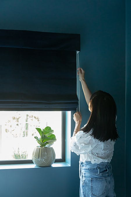 woman opening navy velvet roman shades in dark blue bedroom