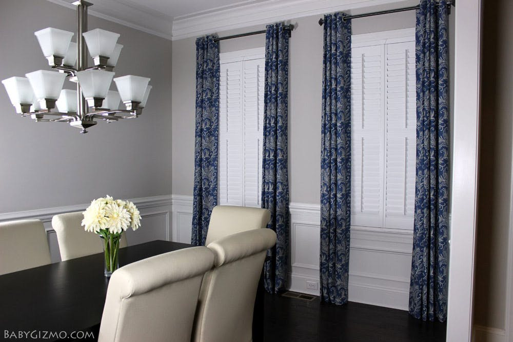 dining room with shutters and blue drapes