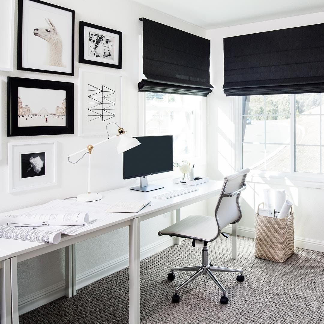 Monochrome black and white office with black roman shades on the windows.