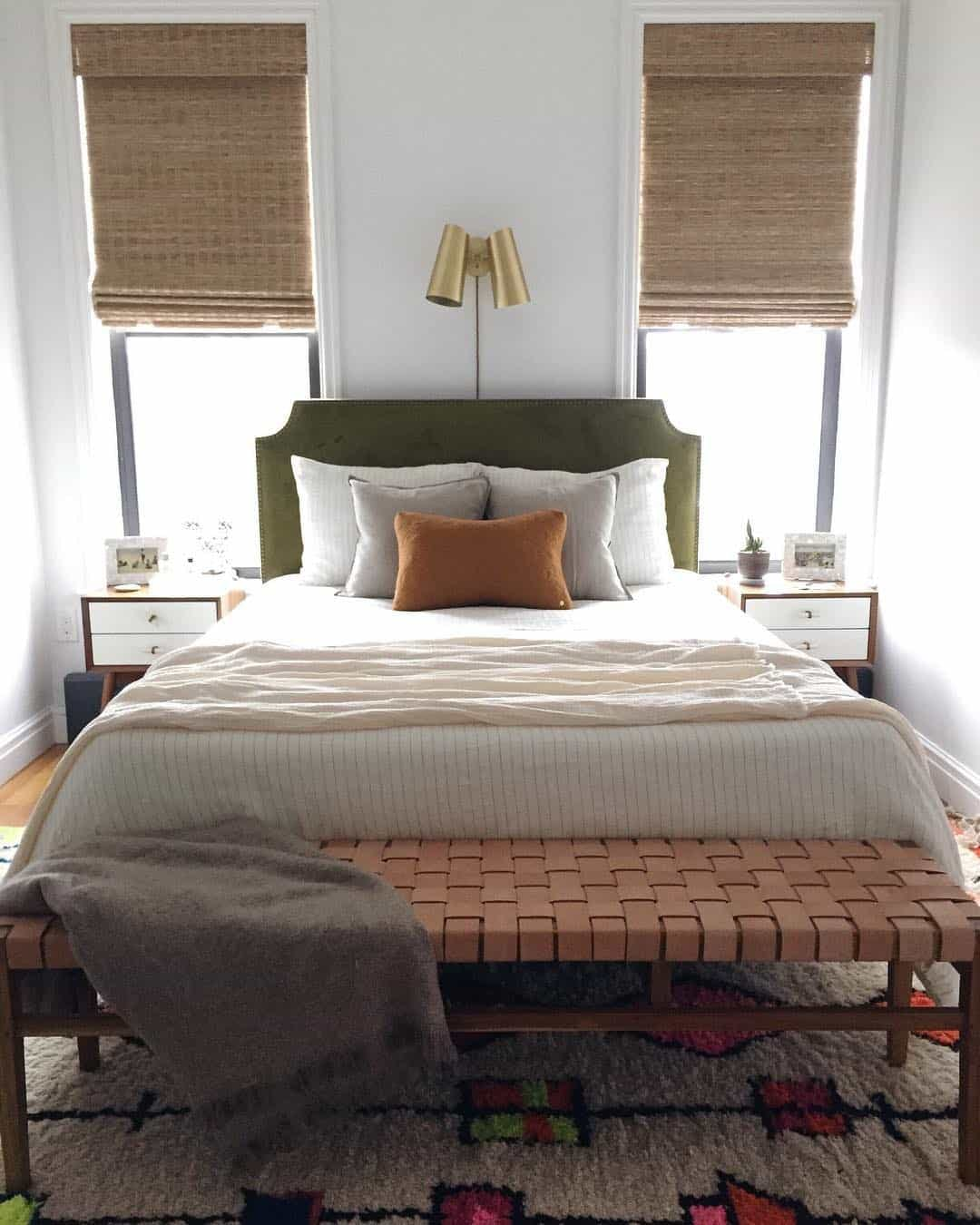 Bedroom with wood furniture, sage green, velvet headboard and woven wood window shades.