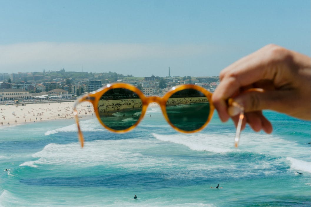 hand holding up sunglasses in front of bondi beach ocean view